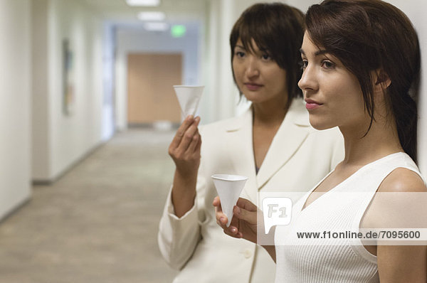 Businesswomen taking break and drink from disposable cups in hallway