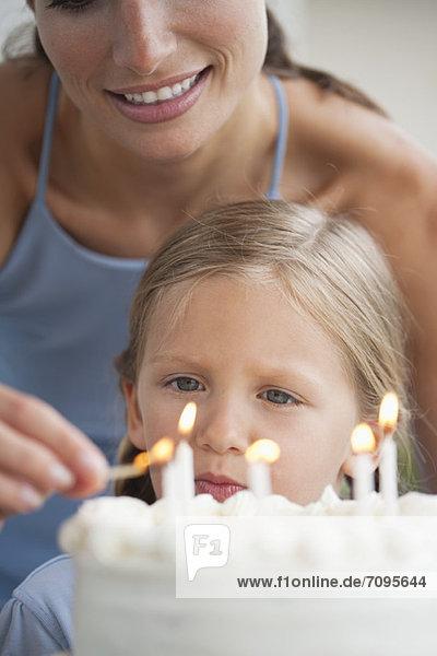 Mutter entzündet Kerzen auf Geburtstagskuchen für Mädchen