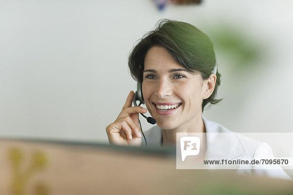 Frau mit Headset  fröhlich lächelnd