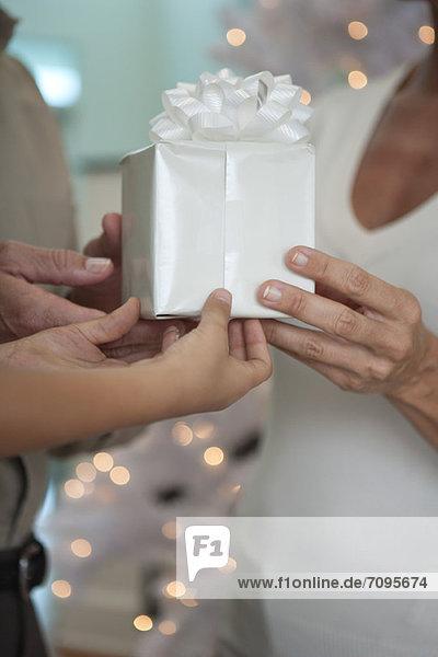 Mann  Frau und Kinderhände halten das Geschenk zusammen  abgeschnitten