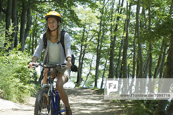 Young woman riding bicycle in woods