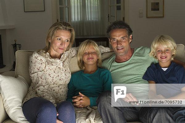 Familie sitzt zusammen auf dem Sofa und schaut fern.