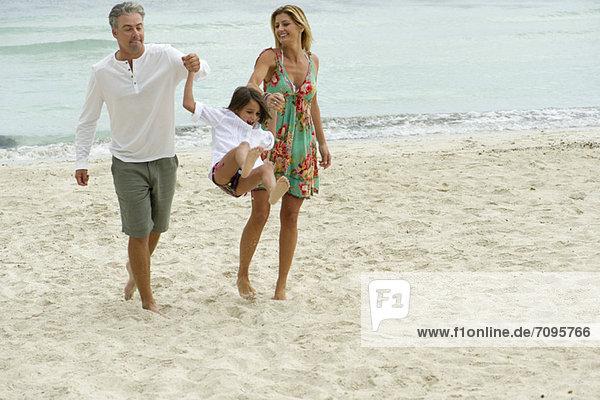 Eltern schwingen ihre kleine Tochter beim Spaziergang am Strand.