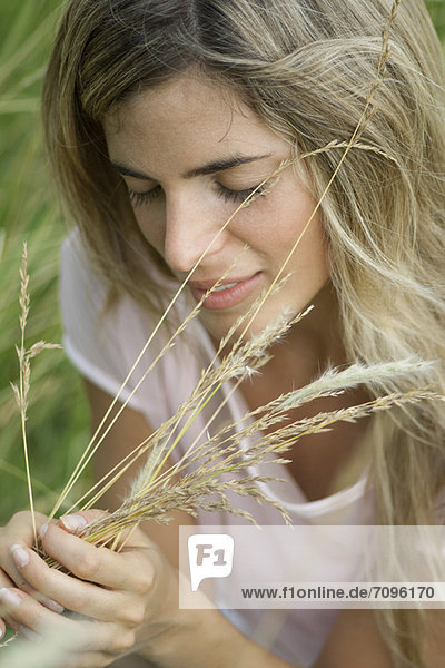 Young woman holding grass with eyes closed
