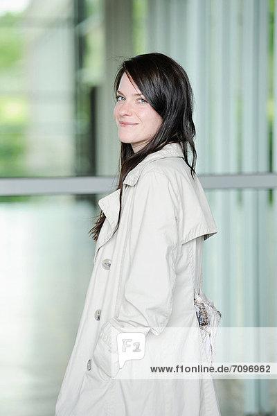 Lächelnde Frau im Trenchcoat