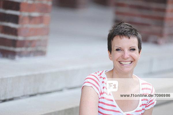 Lächelnde Frau sitzt auf der Stadtstraße
