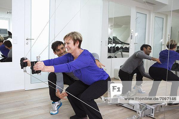 Trainerin bei der Anpassung der Frauenform im Fitnessstudio