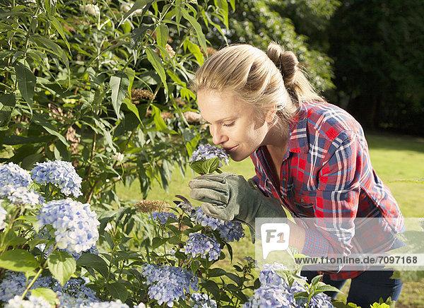 Frau riecht Blumen im Garten