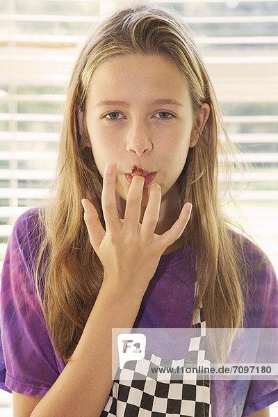 Mädchenverkostung Kuchenglasur in der Küche Mädchenverkostung Kuchenglasur in der Küche