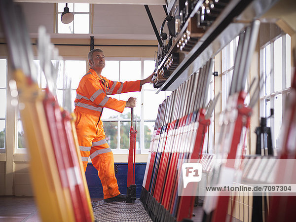 Railway worker pulling track lever