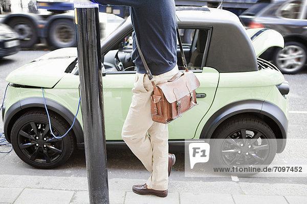 Mann lädt Elektroauto auf der Stadtstraße auf