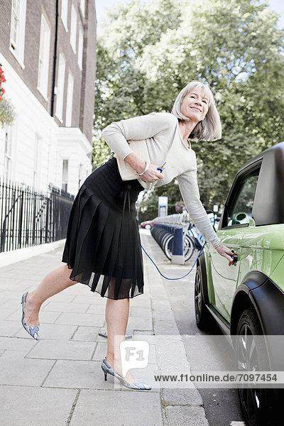 Frau öffnet Autotür auf der Stadtstraße