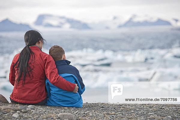 Mother and son admiring glacial lake