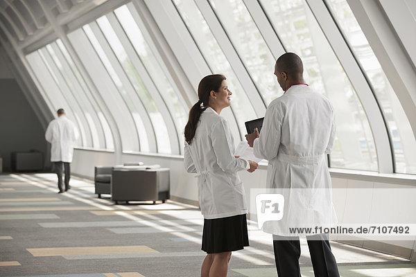 Ärzte sprechen zusammen im Korridor Krankenhaus