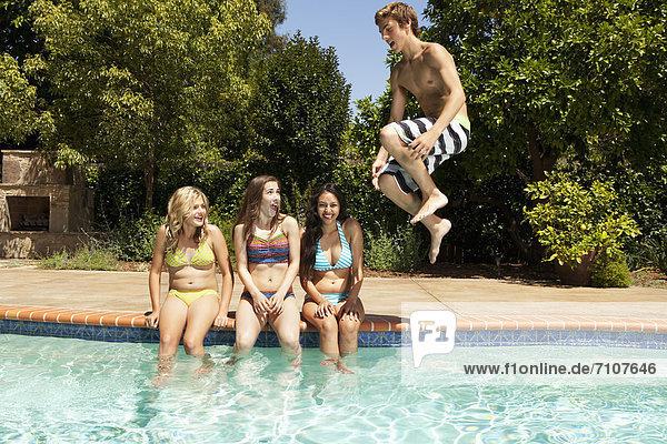 Girls watching teenage boy jumping in to swimming pool