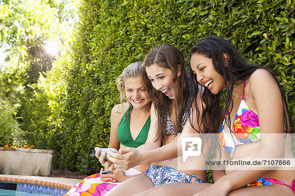 Friends sitting by pool looking at cell phone