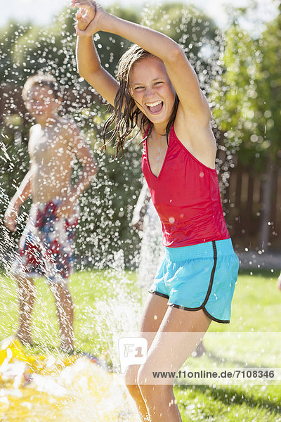 Caucasian girl playing in sprinkler