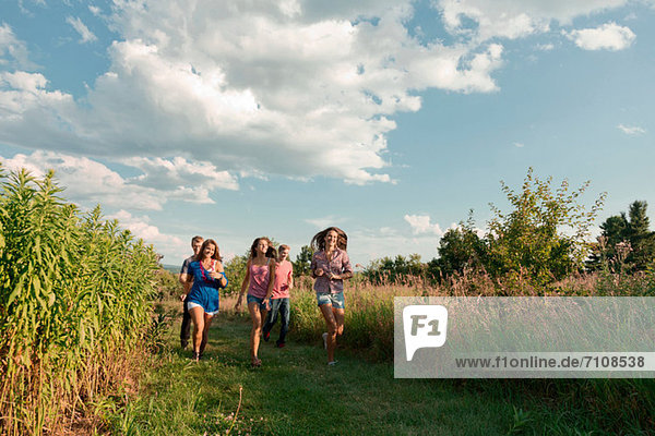 Five friends running through field