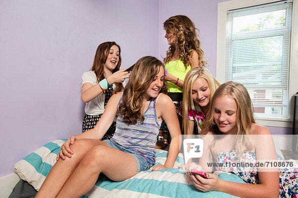 Girls using smartphone in bedroom