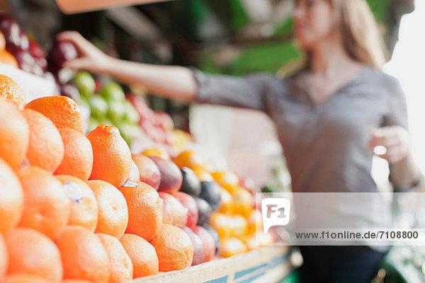 Junge Frau pflückt Früchte aus dem Stall