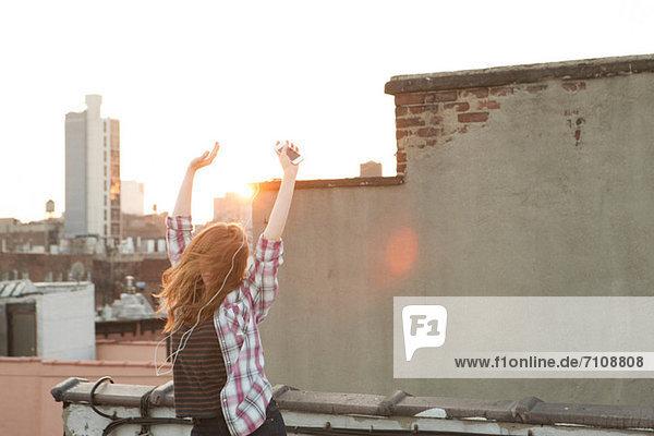 Junge Frau hört Musik mit erhobenen Armen auf dem Dach der Stadt Junge Frau hört Musik mit erhobenen Armen auf dem Dach der Stadt