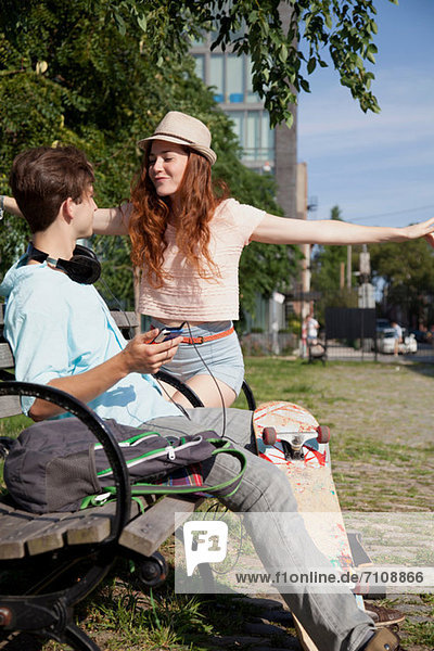 Junges Paar auf der Bank beim Musikhören