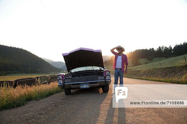 Mann und Auto mit Motorhaube oben