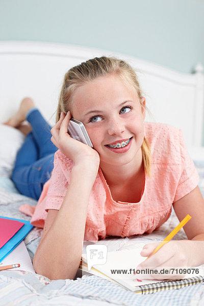 Teenager Mädchen auf dem Handy mit Notizblock