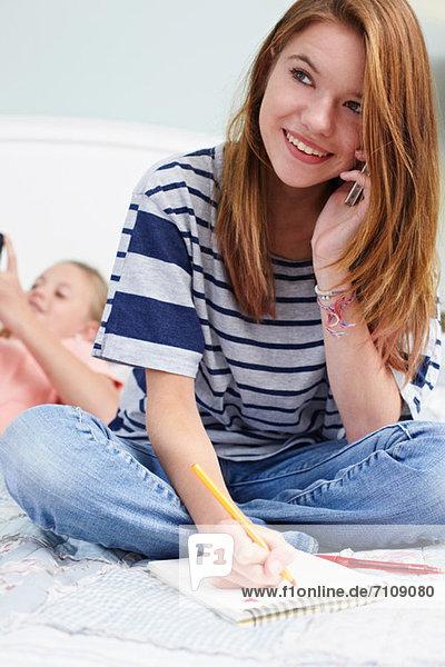 Teenager-Mädchen auf dem Bett sitzend mit Notizblock  über Handy