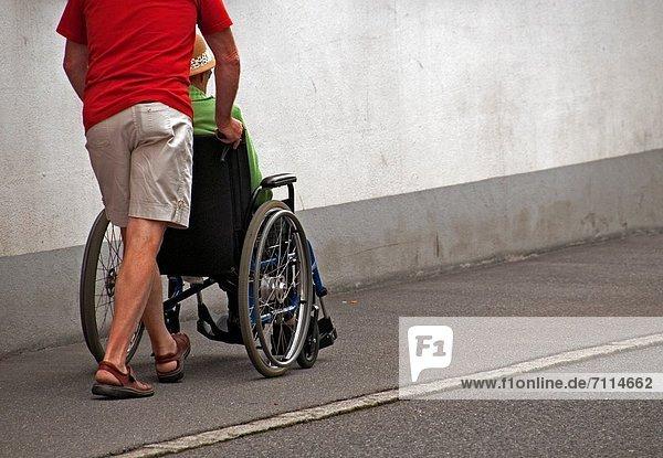 Städtisches Motiv  Städtische Motive  Straßenszene  Straßenszene  Mann  schieben  Sommer  Mittelpunkt  Lebensphase  Schweiz  Rollstuhl