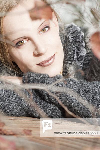 Blonde junge Frau lehnt auf einem Holztisch im Freien