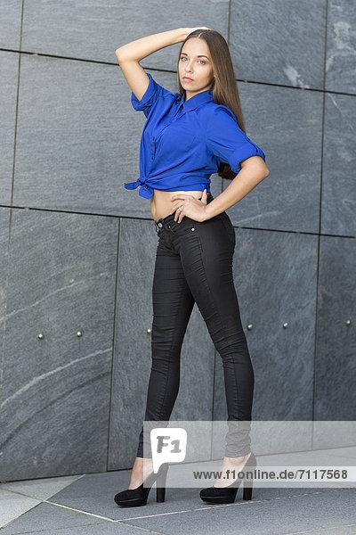 Pumps hoch oben junge Frau junge Frauen Steinmauer Pose grau schwarz frontal blau Jeans Kleidung