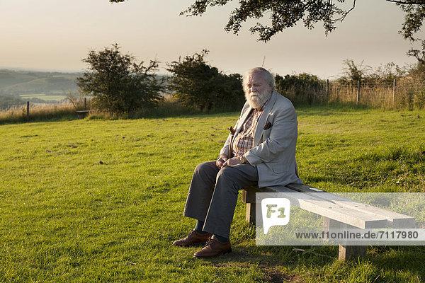 Ein älterer Mann sitzt auf einer Bank in einem Landschaftspark  Buriton  Hampshire  England  Großbritannien  Europa