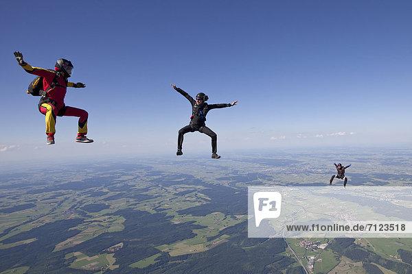 Drei Fallschirmspringer in der Luft  Bayern  Deutschland