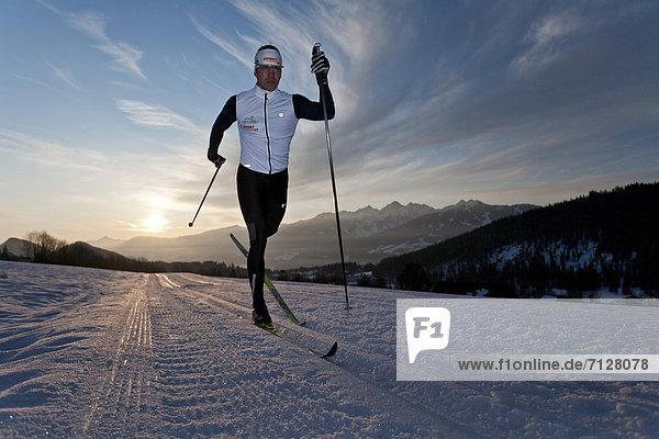 Wintersport  Winter  Mann  Sport  Morgen  Skisport  Ski  Langlaufski  Ramsau bei Berchtesgaden  Österreich  Abenddämmerung  Dämmerung