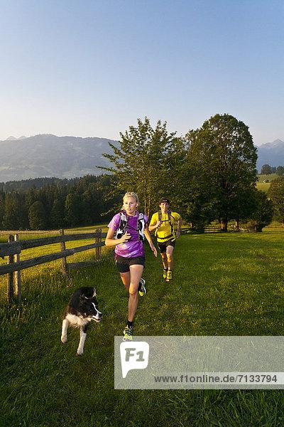 Frau  Mann  Sport  gehen  folgen  Gesundheit  rennen  Hund  Wiese  joggen  Ramsau bei Berchtesgaden  Österreich