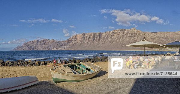 Spain  Lanzarote  La Caleta  Outdoor  cafe  Risco de Famara  landscape  water  summer  mountains  sea  people  ships  boat  Canary Islands