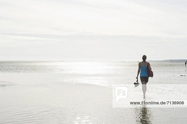 Junge Frau bei einer Wattwanderung  Wyk  Föhr  Nordfriesland  Schleswig-Holstein  Deutschland  Europa