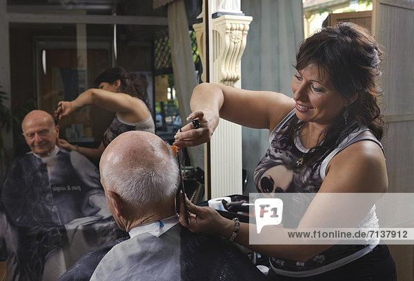 Ein alter Mann ist im Friseursalon  Schneiden der Haare  Baden-Württemberg  Deutschland  Europa