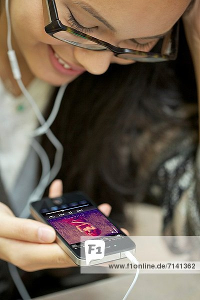 benutzen  4  zuhören  lächeln  Kopfhörer  Musik  jung  Kleidung  Iphone