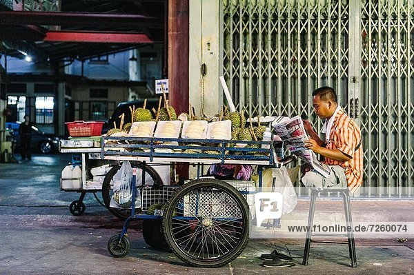 A street vendor reads a newspaper while sitting behind his push cart