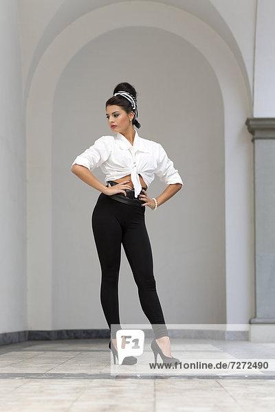 Junge Frau mit Hochsteckfrisur  weißem Hemd  schwarzen Leggins und hohen Schuhen