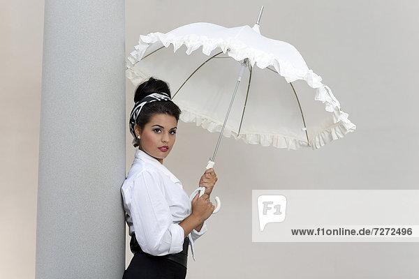 Junge Frau mit Hochsteckfrisur  weißem Hemd und weißem Schirm