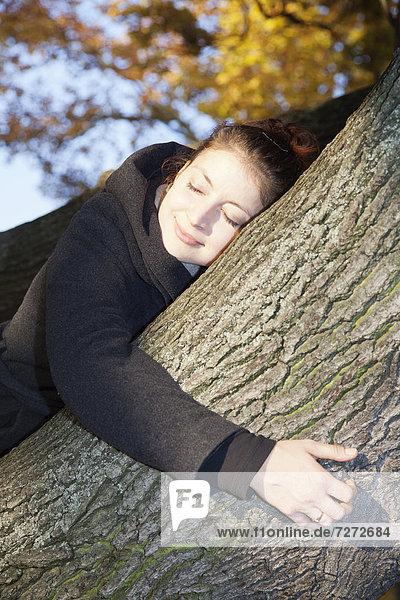 Junge Frau mit geschlossenen Augen auf einem Baum im Herbst