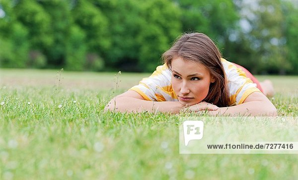 Pensive woman lying in park