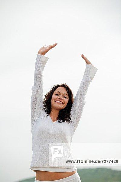 Portrait  Frau  Frische  lächeln  Meer  braunhaarig  Blick in die Kamera  Himmel  ausatmen