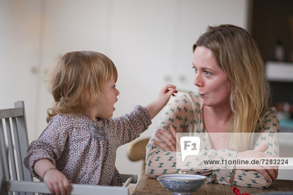 Daughter spoon feeding mother