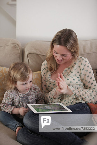 Mother and daughter playing with digital tablet