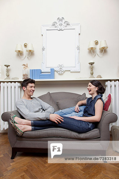 Paar lachend auf dem Sofa