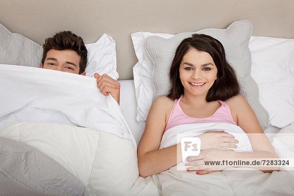 Paar im Bett  Mann schaut hinter die Bettdecke
